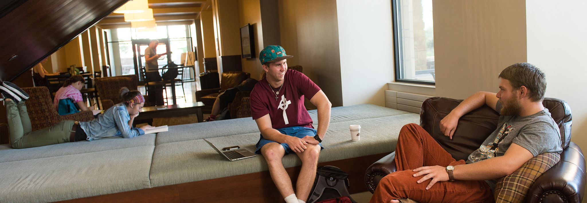 Two students are lounging in Leprino Hall at CCU.