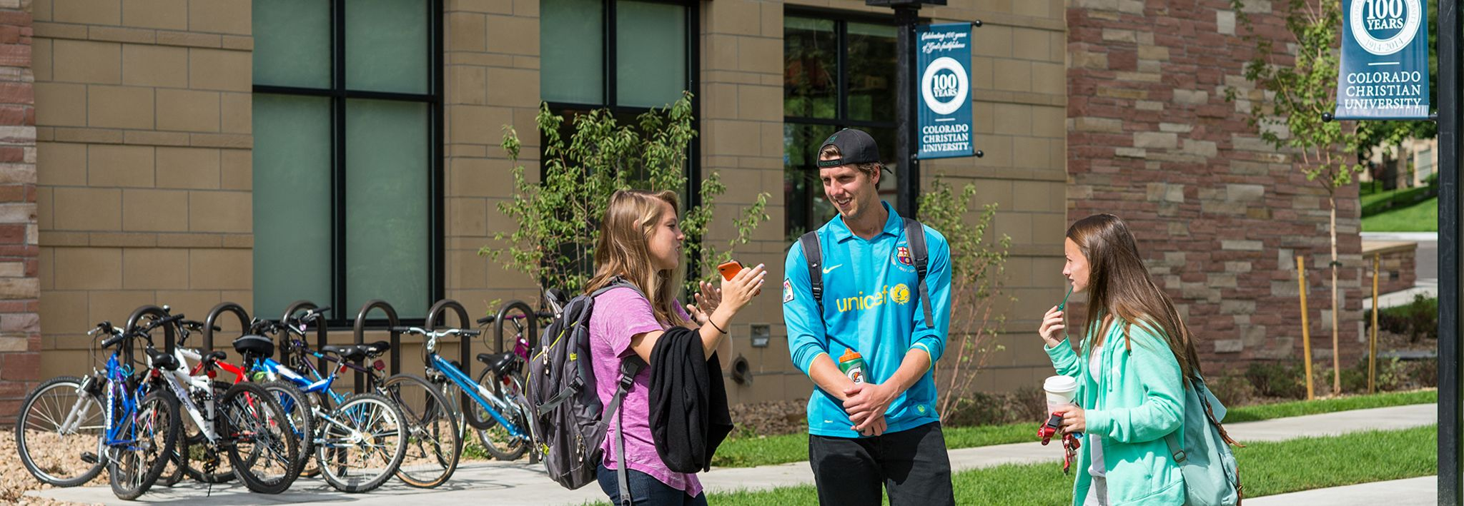 A group of students are talking outside on the CCU campus.