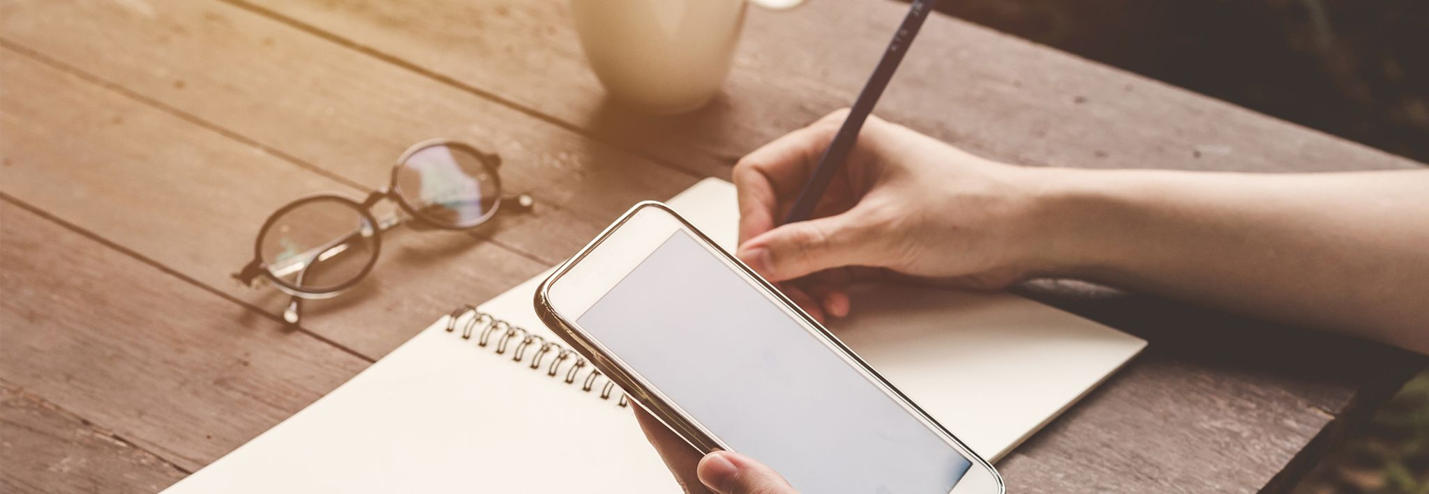 A woman is communicating on her phone while taking notes.