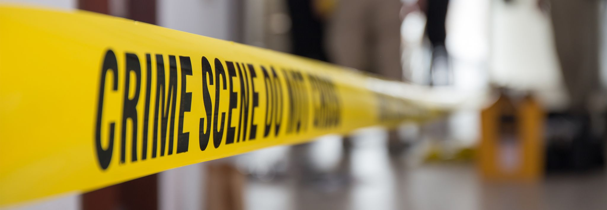 Crime scene tape is up at the scene of a crime.