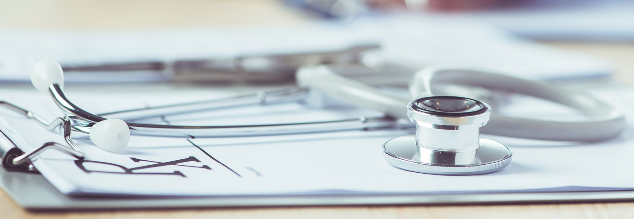 A stethoscope is laying on a doctor's notepad.