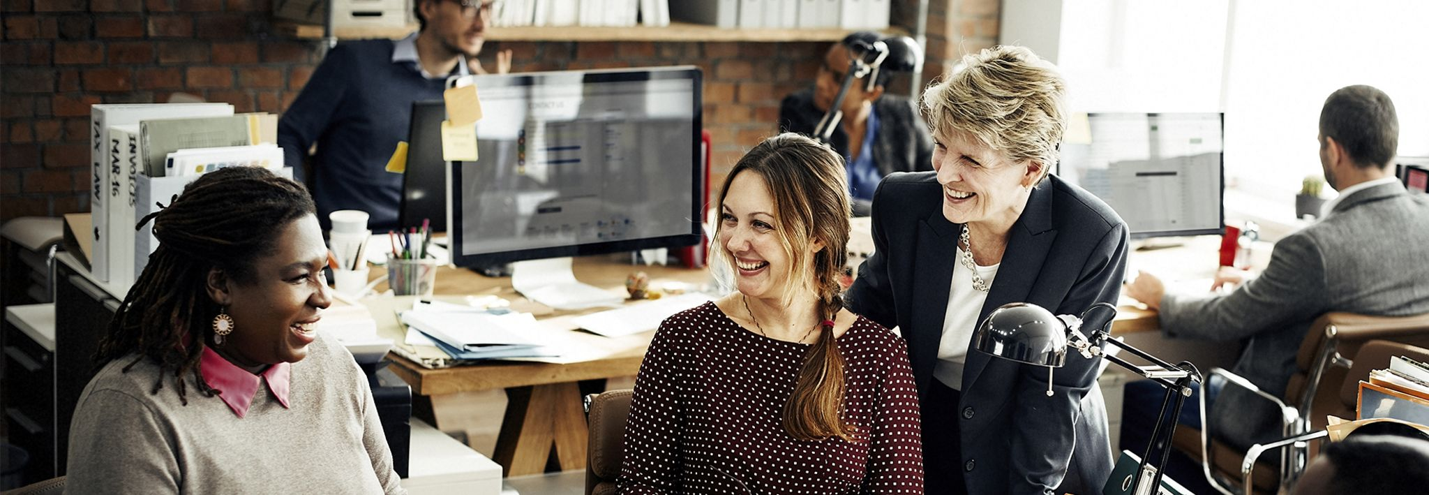 Three female professionals are talking and laughing together at work.