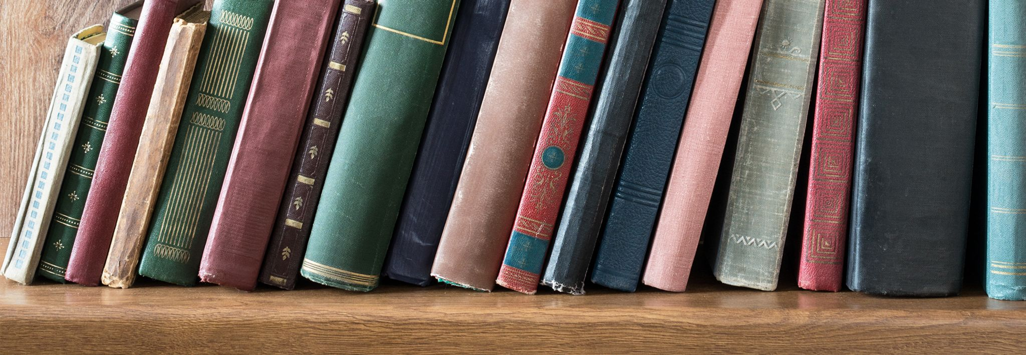 Several general studies books are leaning on a shelf.