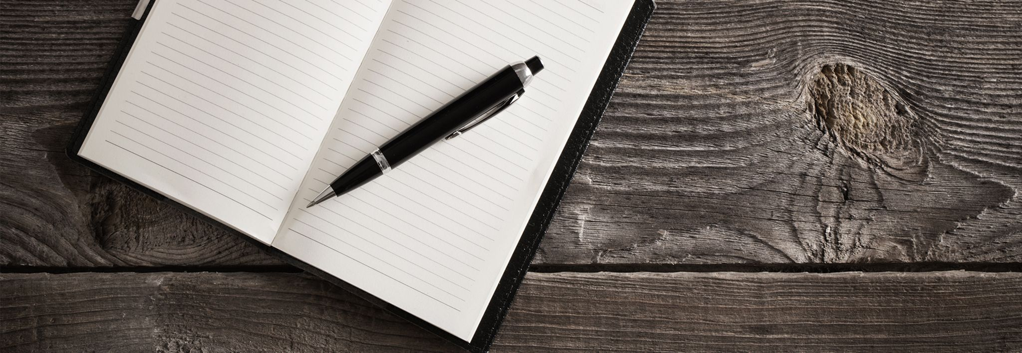 A pen and a notepad are laying on a wooden table.