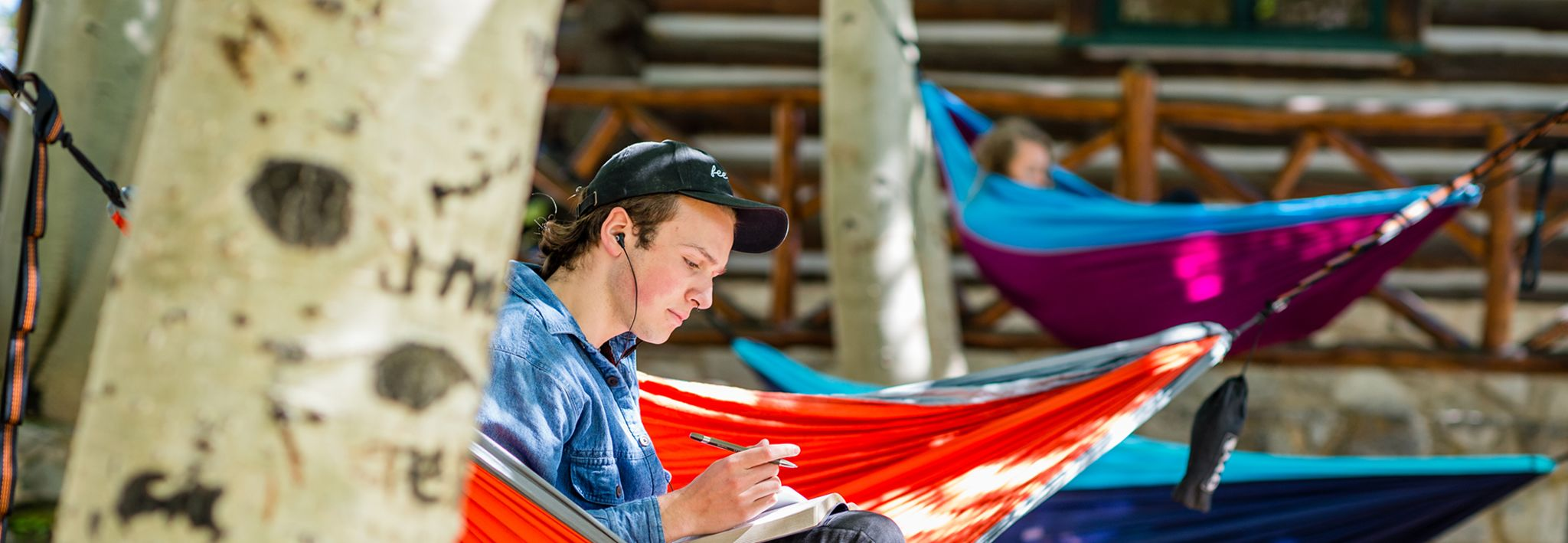 CCU student doing homework in a hammock on a nice, sunny day.