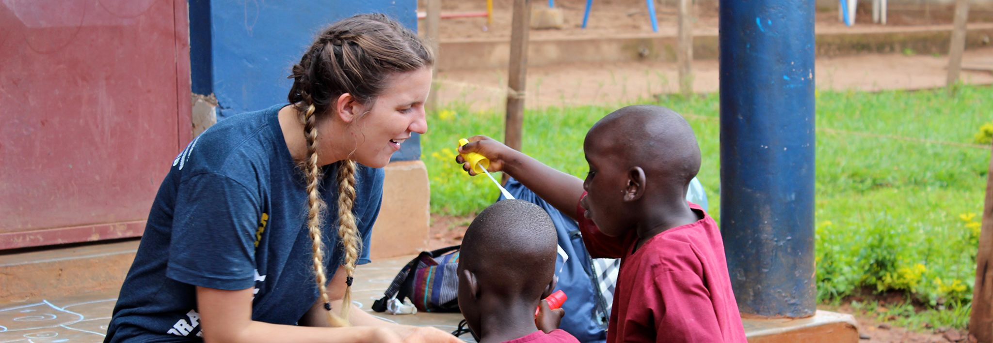 CCU student playing with kids in Uganda.