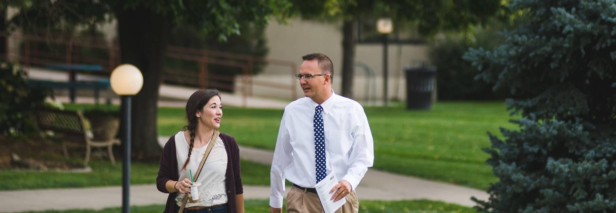 Matt Jones, CCU professor, walking with a student through campus.