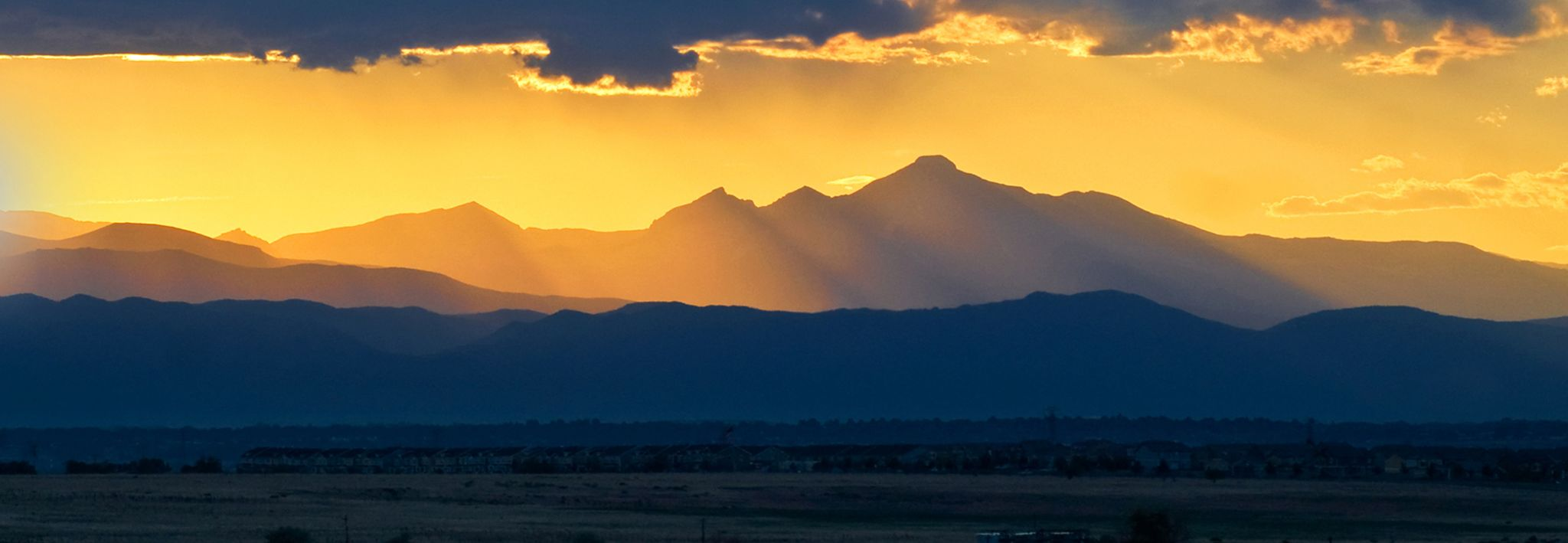 Front range mountains with gold sunlight shining down on it.