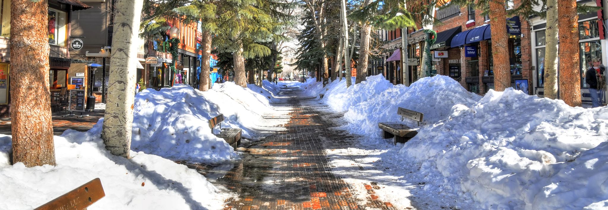 Snow pilled up on the sides of a sidewalk in Aspen, Colorado.