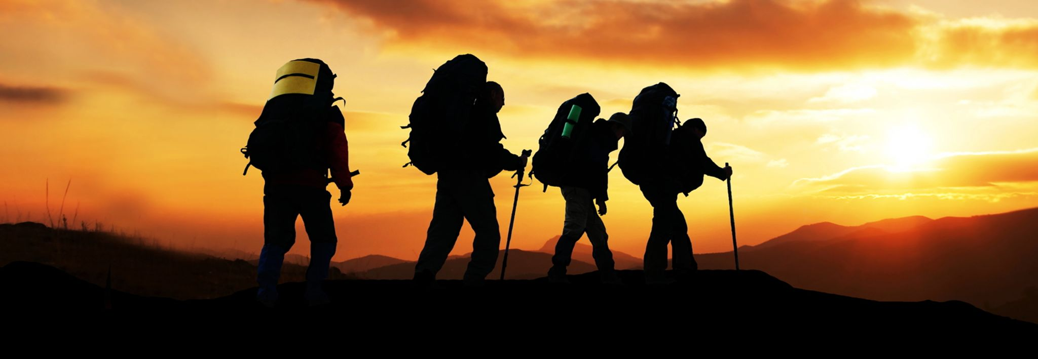 College students hiking at sunset.