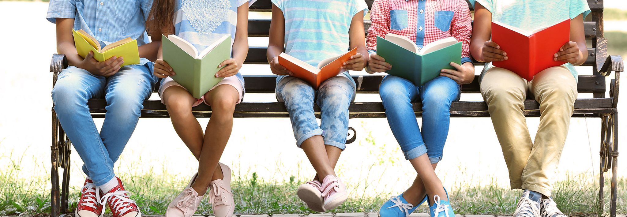 Kids posing for a cute picture on a bench with their books.