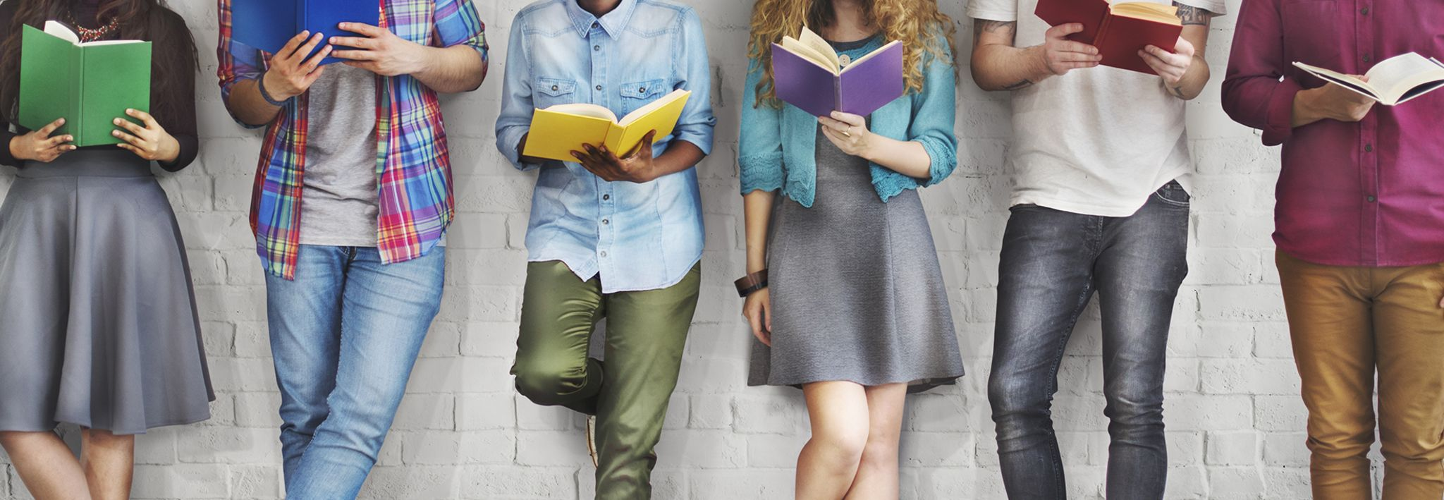 College students posing with colorful books.