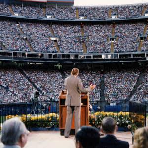Billy Graham in front of Denverites at Mile High Stadium