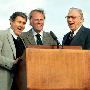 Billy Graham and his team behind a podium