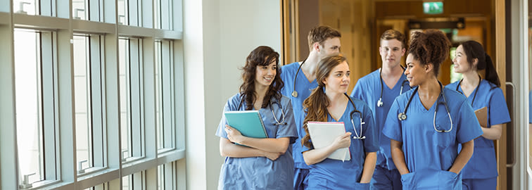 young physician assistants walking together in hospital hallway