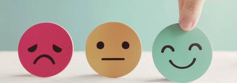 a sad face, smile face, and a grumpy face