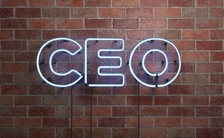 CEO is written on a lit-up sign on a brick wall.