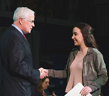 president_handing_student_a_scholarship