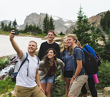 students taking a selfie with mountains in the background