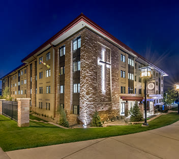 Yetter Hall on CCU campus at night with lit cross