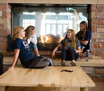 Female CCU students sitting in front of fireplace talking