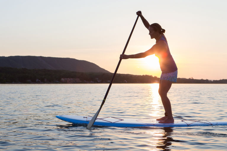 A woman is paddle boarding in the mountains to relieve stress.