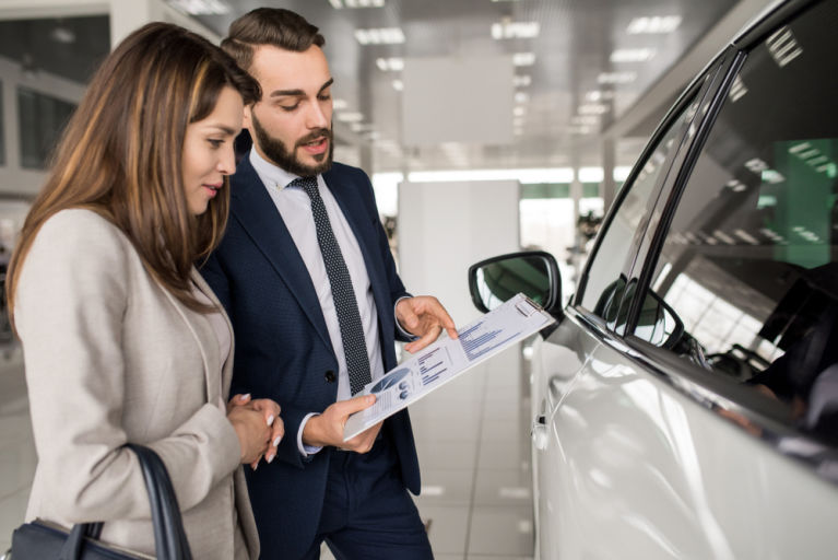 A car salesman is trying to sell a car to a female customer.