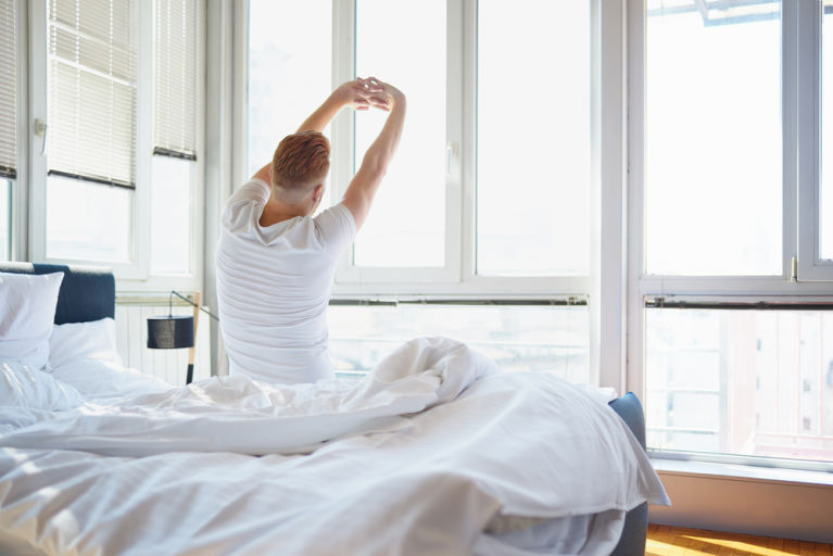 A man is stretching in bed after a good night's sleep.