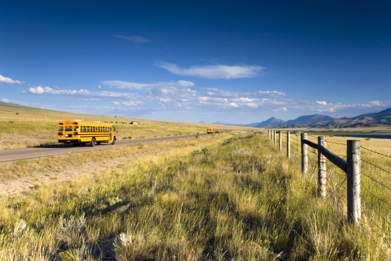A school bus is driving through the country in a rural area.