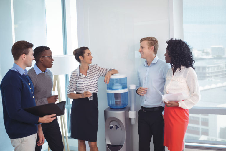 A group of coworkers is chatting at the water cooler at work.