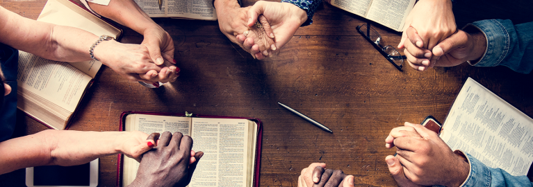 Adult students praying around a table