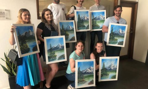 Workshop group photo, class holding up their Bob Ross paintings