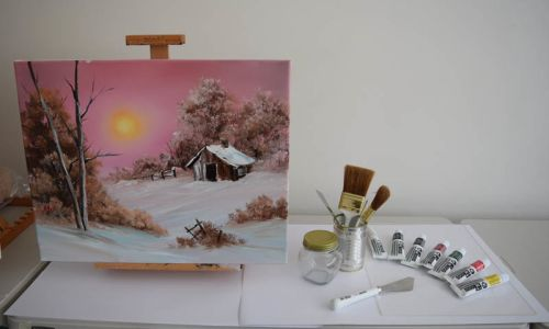 Painting on easel with Bob Ross paints and brushes displayed