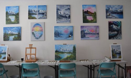Many landscape paintings hanging on the wall, with painting stations set up at on a table