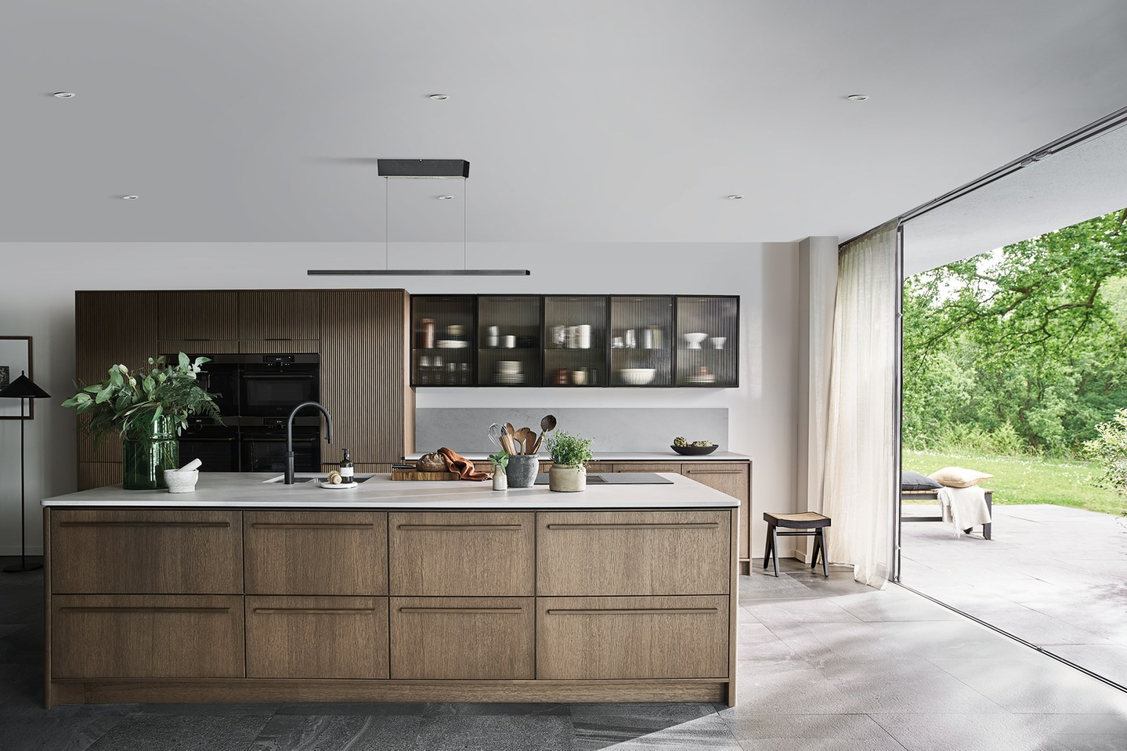 Magnet Kitchens 2021 Nordic Nature range with Fluted oak cabinets with Dekton Aeri worktop. Floating island with boiling hot water tap.