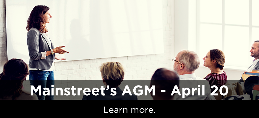 female teacher standing in front of an adult classroom - heading text reads 'Mainstreet's AGM - April 20' and a description of 'Board voting - March 29-April12'