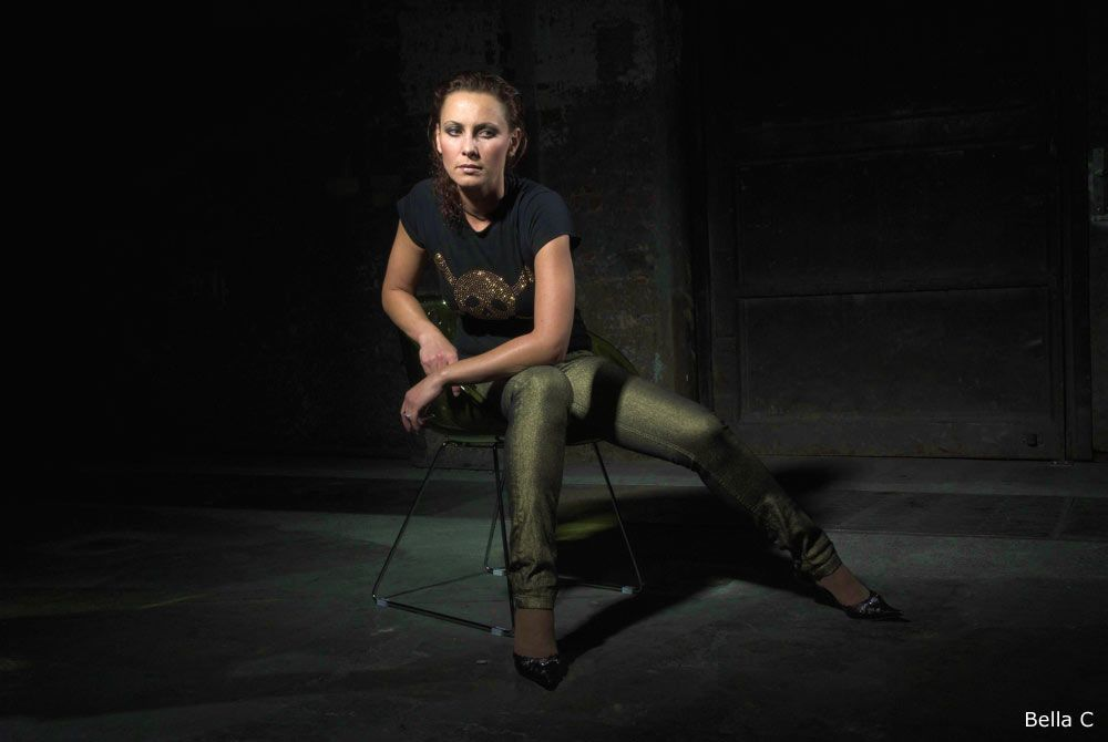 Bella C. with tight trousers, black shirt, sitting
