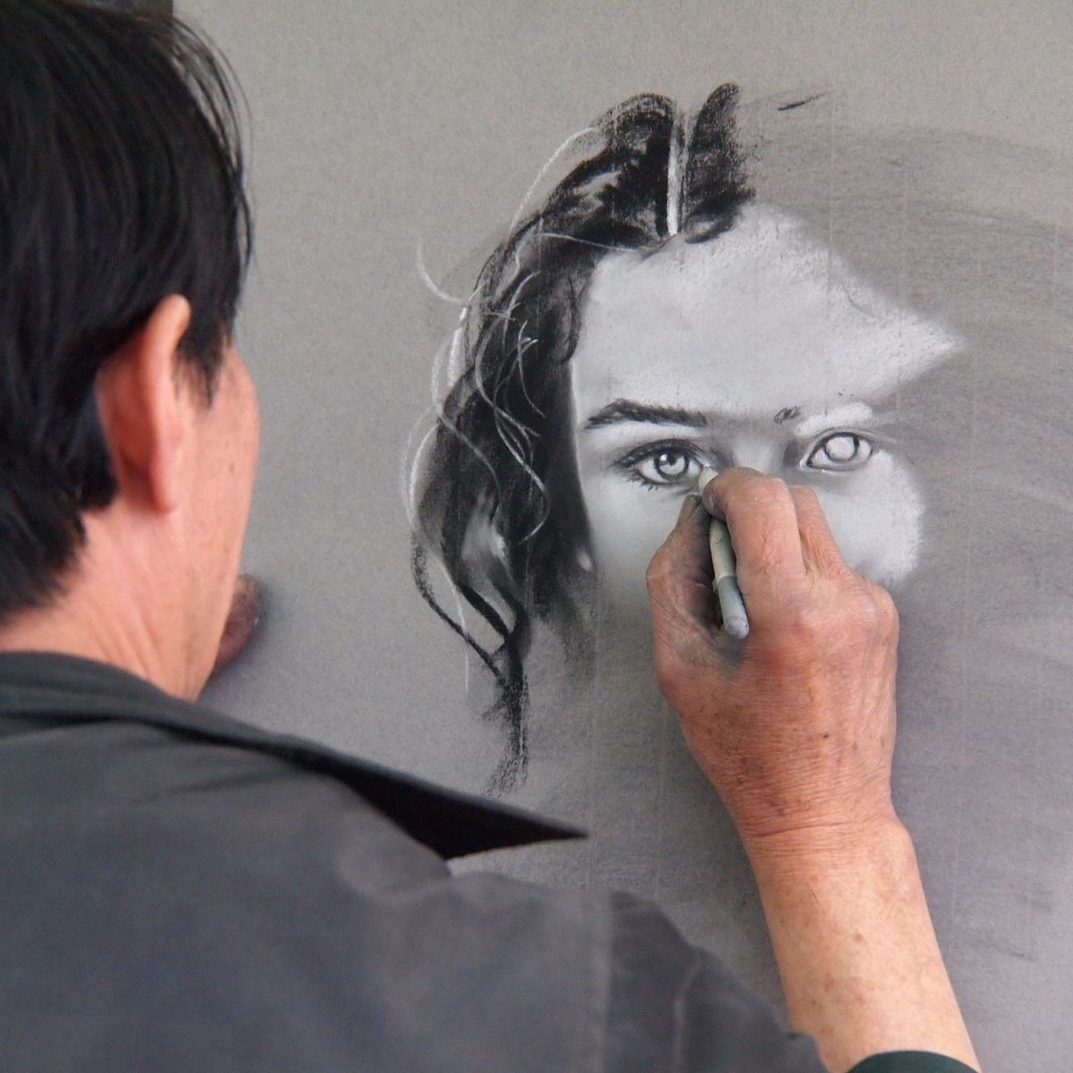 Artist draws sketch of woman on wall