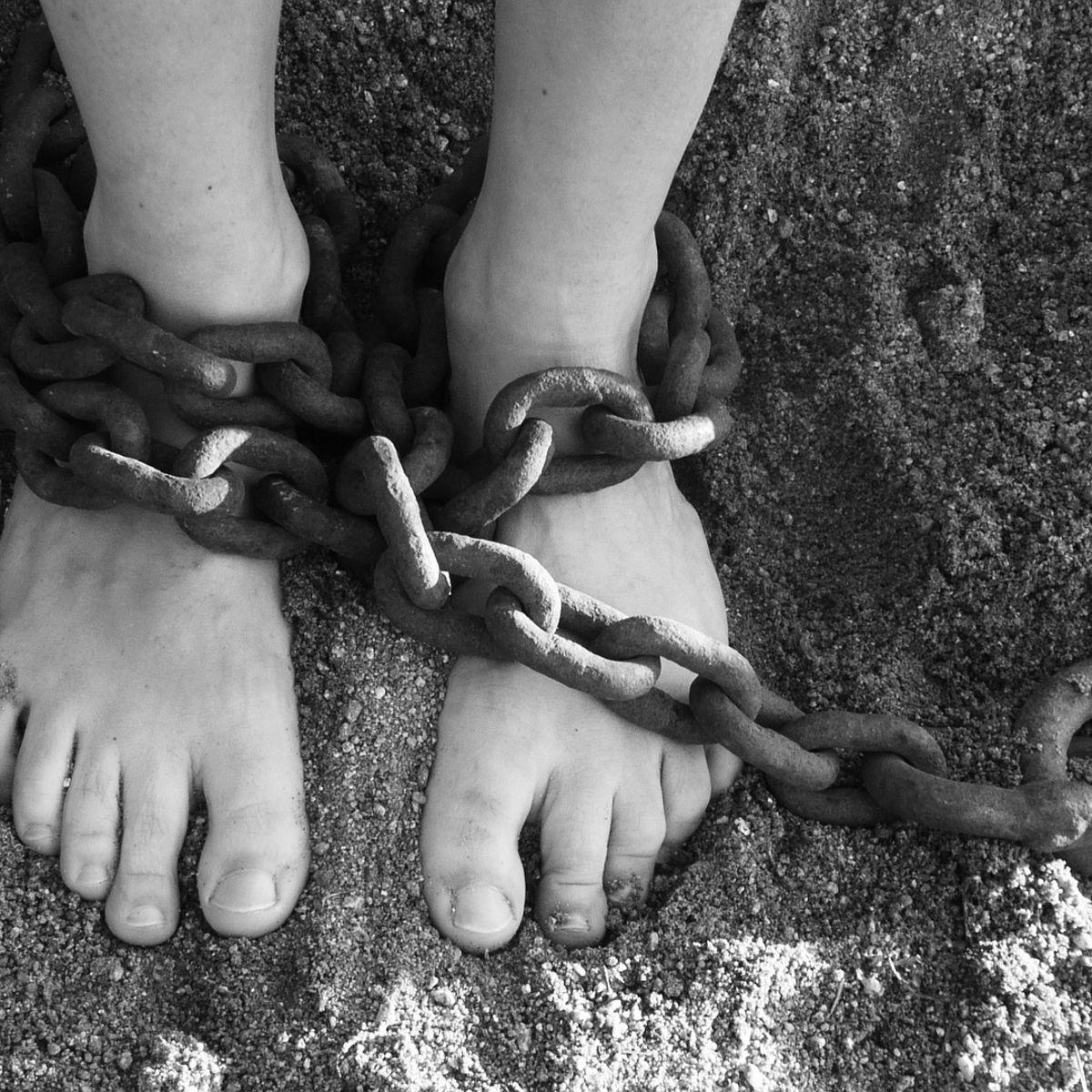 Slavery with chains around feet, bondage