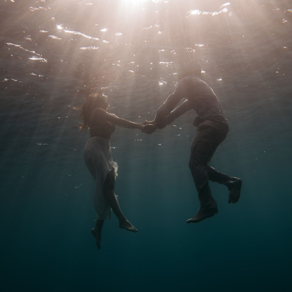 Couple swimming underwater in sea, lake