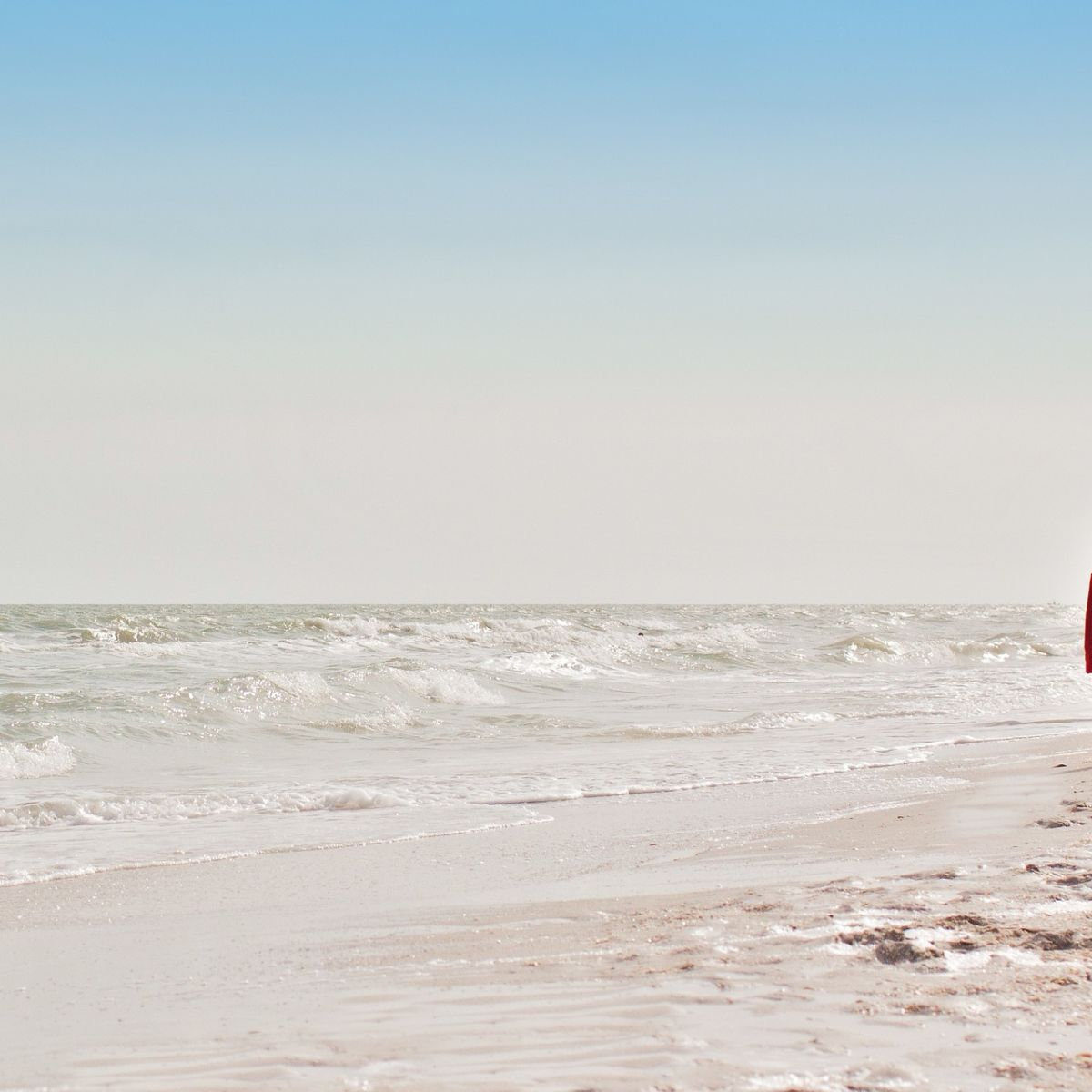 Youn girl at the beach looking into the sea and horizon