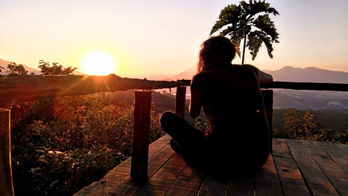 Relaxing in sunset: Woman meditating peacefully