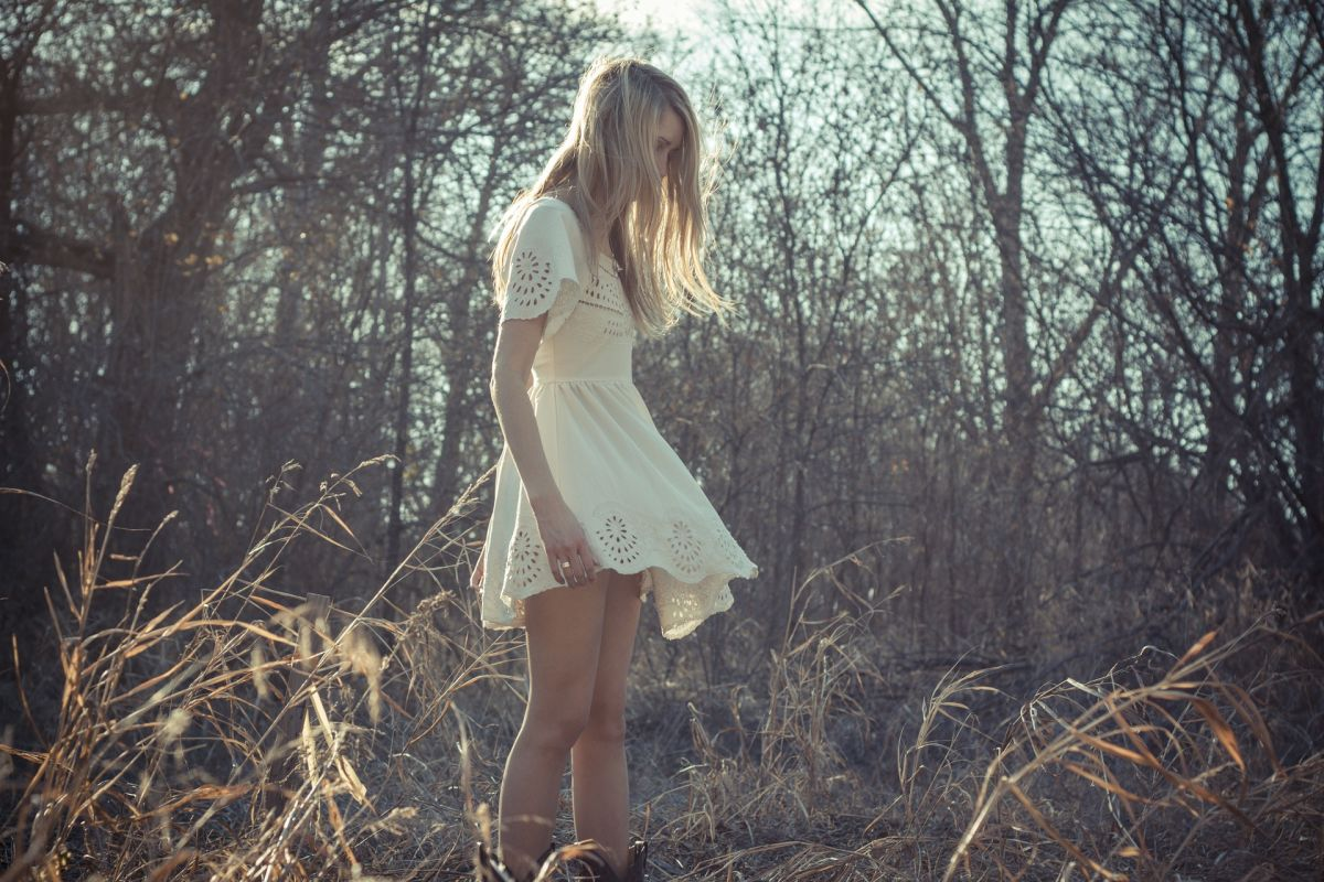 Woman with white dress and long blonde hair in forest