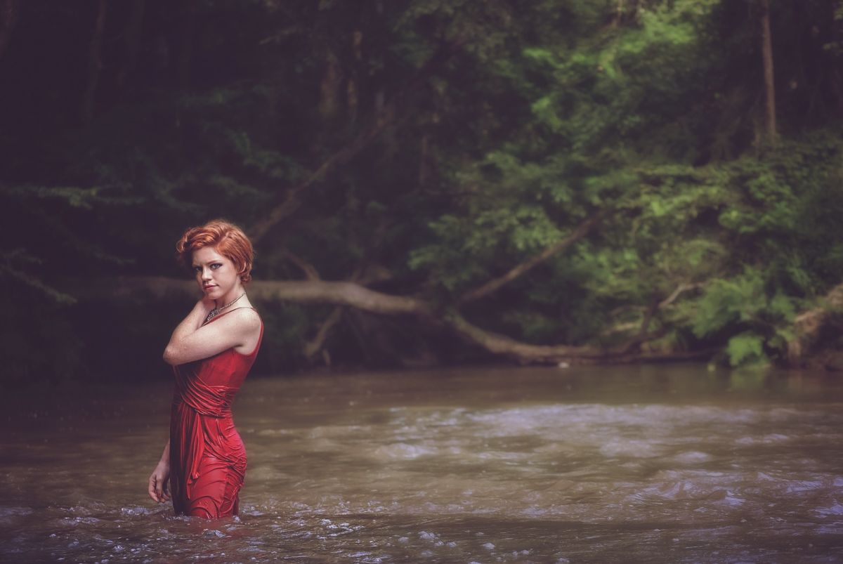 Woman with red dress in river and forest