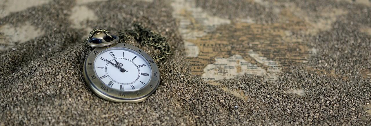 Pocket watch on sandy beach