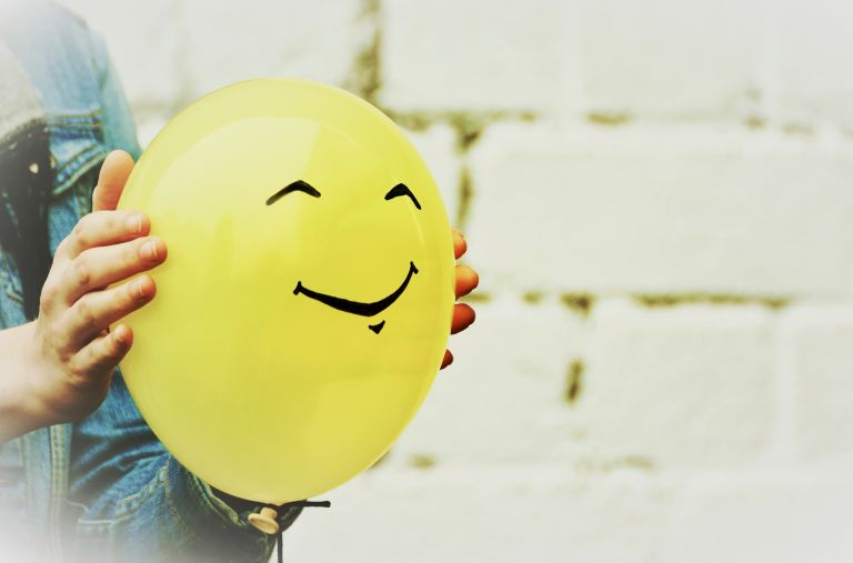 Hands holding yellow smiling balloon.