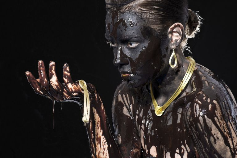 Woman full with black chocolate and gold jewellery