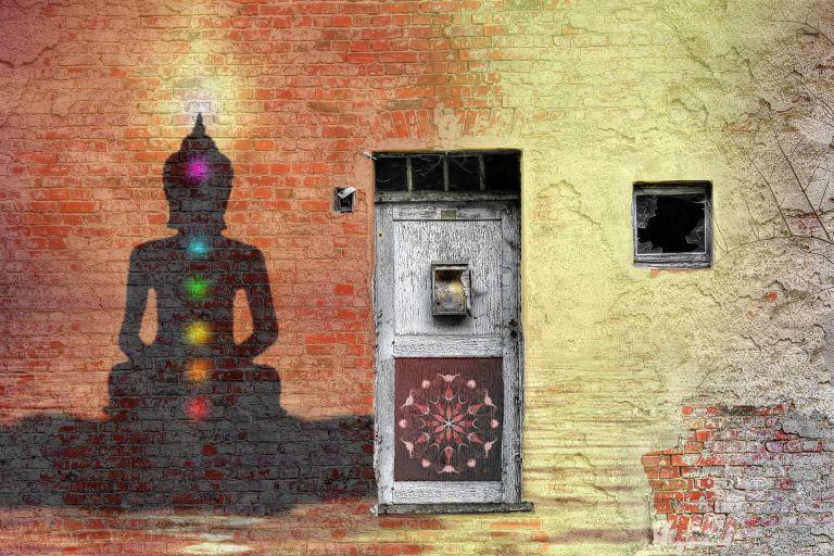Chakras and mandala graffiti on a wall with door