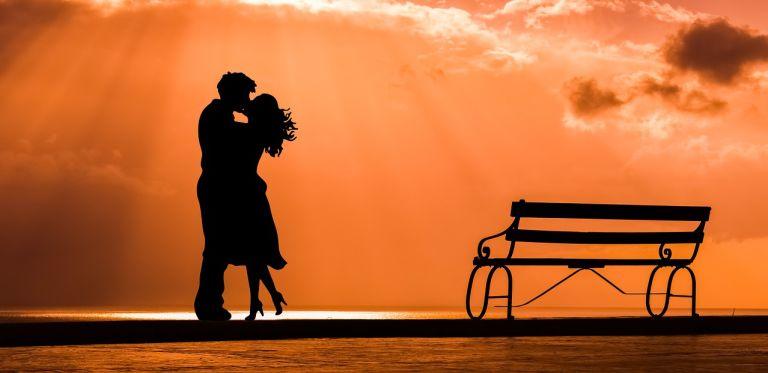 Romance loving couple in orange sunset with bench