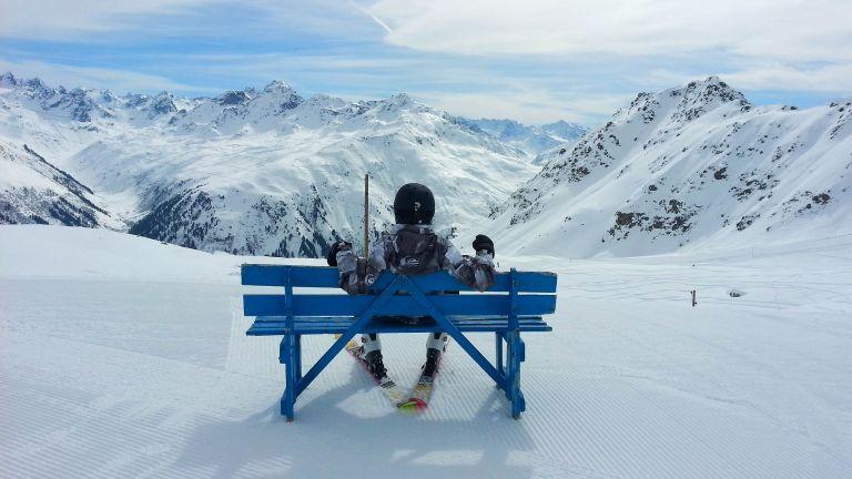 Mountains in Switzerland, Davos. Man with ski sitting on bench.